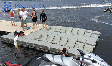 Gray plastic HDPE floating dock pontoon cubes attached to a dock with people standing