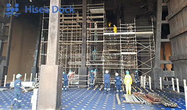 An image of workers standing on a platform for scaffolding