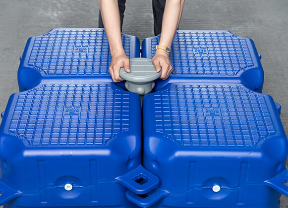 A person assembling a plastic floating dock