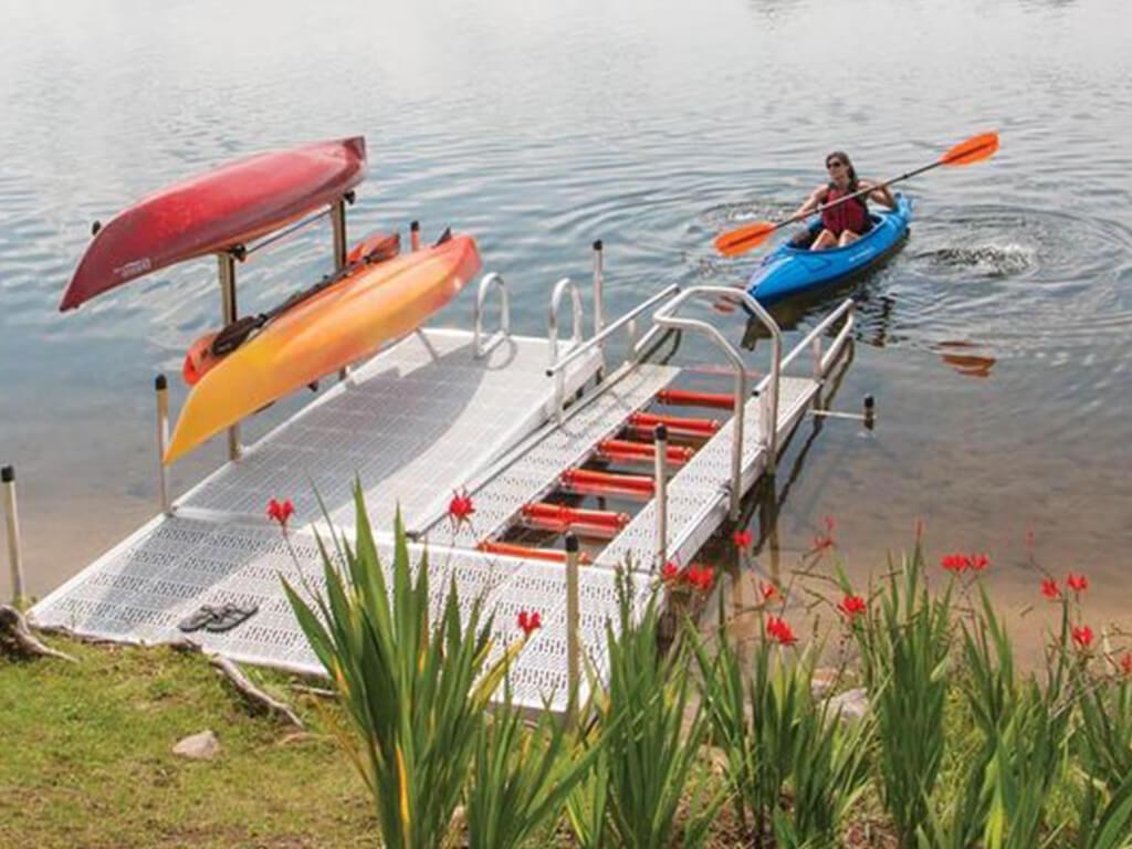 A girl kayaking near a kayak dock