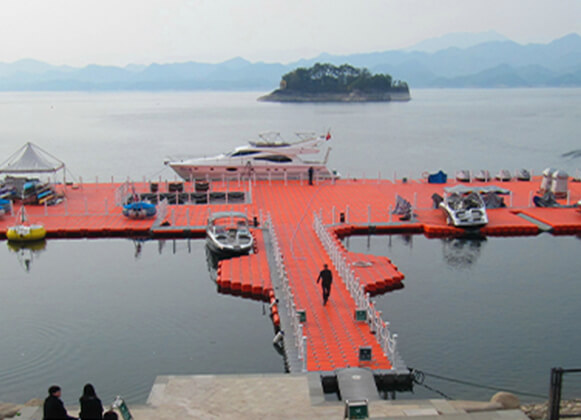 Boats and a yacht docked alongside a large floating bridge