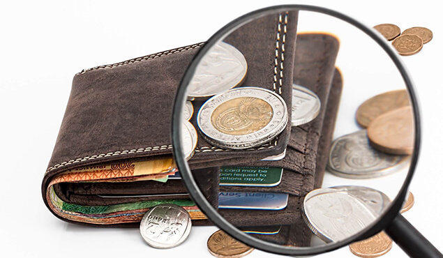 An image of a magnifying glass focused on a brown wallet with the coins outside