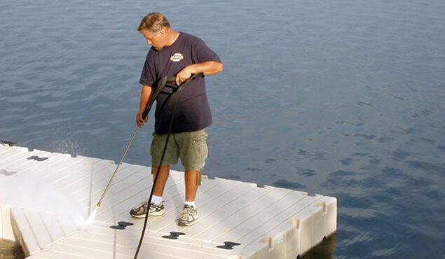 A man power washing a floating platform