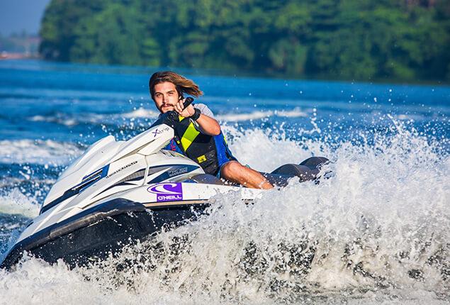 Man in safety vest riding a jet ski