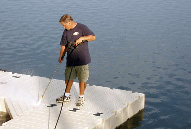 A man power washing a white floating dock