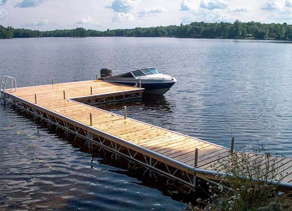 A boat docked at a wooden pipe dock