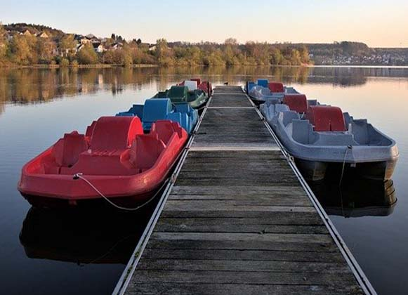 Boats Lined Up Along A Wooden Dock