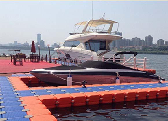 A yacht and a motorboat docked alongside a floating drive-on dock