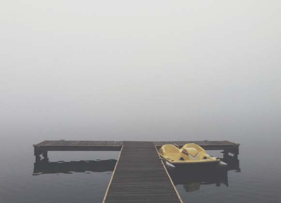A Paddle Boat Anchored to a Wooden Dock