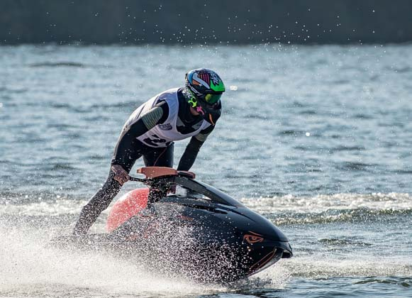A man complete with protective equipment riding a jet ski