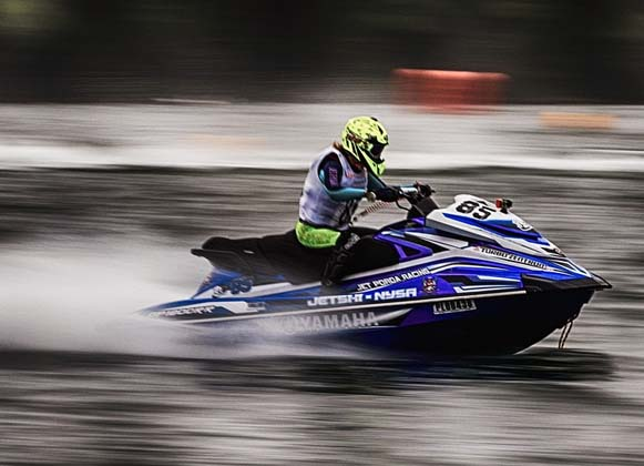 Person riding a fast-moving personal watercraft