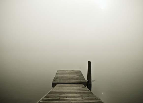 A brown dock at a foggy lake