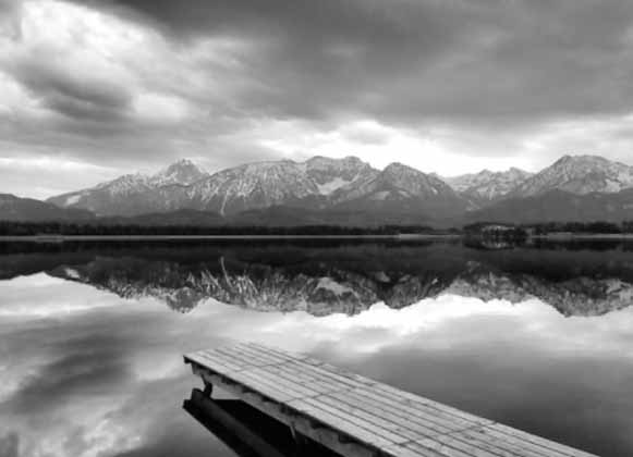 A black and white image of a dock on a river