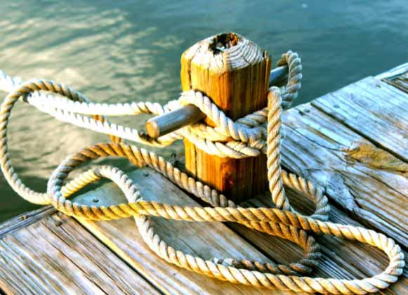 An close up image of a rope tied on a wooden dock