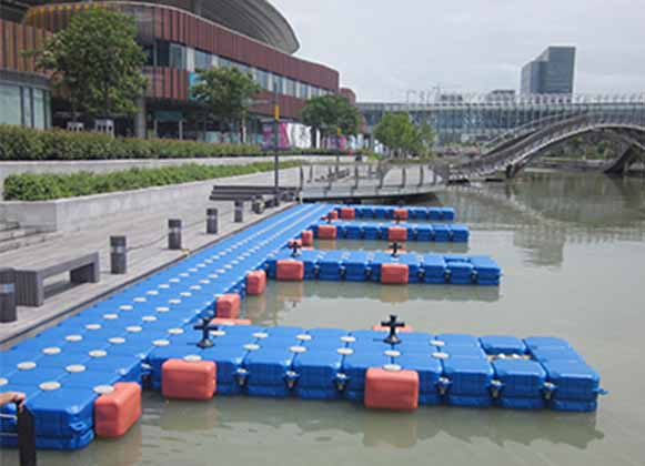 A plastic floating dock installed near a building