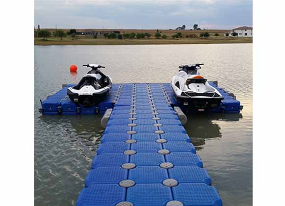 Two jet skis docked at a plastic floating dock